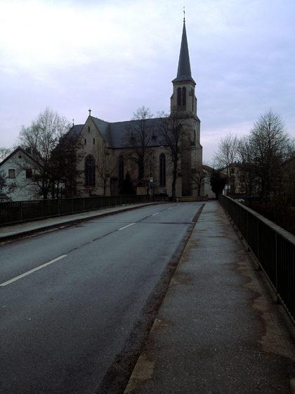 Ich überquere eine Brücke über die Nied und gehe an der Kirche St. Rufus vorüber