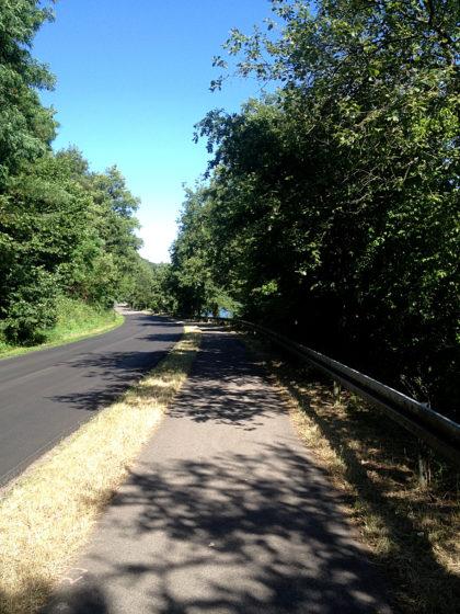 Hinter der Leitplanke der Fluss, links eine Landstraße ohne Mittelstreifen