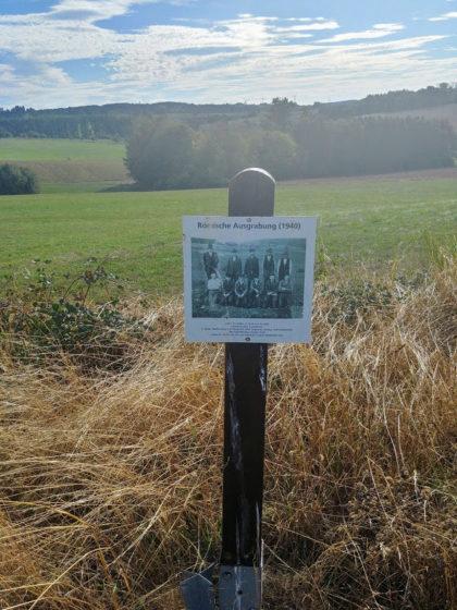 Am Wegrand das Schwarzweißfoto einer Gruppe von Männern, die 1940 in der Gegend hier einen Gutshof aus dem 4. Jahrhundert ausgegraben hat